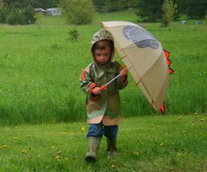 Puzzle Boy avec son parapluie et une veste imperméable sous la pluie de printemps