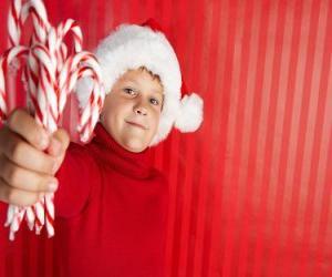 Puzzle Enfant avec un chapeau de Père Noël et des cannes de bonbon à la main