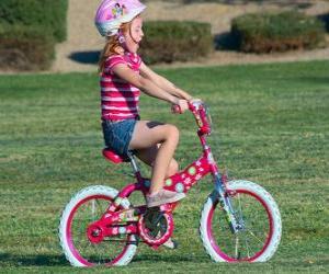 Puzzle Fille à bicyclette dans le parc au printemps