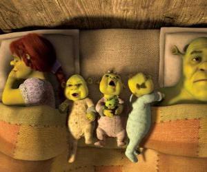 Puzzle La famille de Shrek, Fiona et trois ogres jeunes dans son lit.