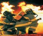 Pompier avec un genou sur le sol et le tuyau prêt