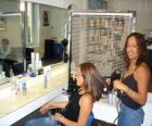 Coiffeur en paignant et en séchant des cheveux à une costumer dans le salon de coiffure ou salon de beauté