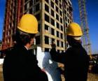 Technicien en consultant un plan dans le travail de bâtiment - Architecte, agent de maîtrise ou ingénieur