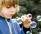 Enfant jouant à faire des bulles de savon