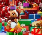 Ours en peluche avec vêtement de Père Noël et avec les cadeaux de Noël