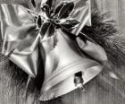 Cloche de Noël décoré de feuilles de houx et un ruban avec un grand nœud