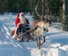 Le Père Noël dans son traîneau avec un renne sur la neige