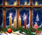 bougies de Noël allumé devant une fenêtre
