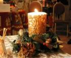 Bougie allumée comme une décoration centrale ornée de branches de houx et de sapin