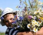 Un enfant avec un cadeau pour sa mère, un grand bouquet de fleurs