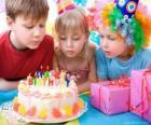 Fille dans le moment de souffler les bougies de son gâteau d'anniversaire