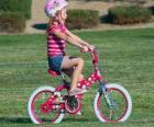 Fille à bicyclette dans le parc au printemps